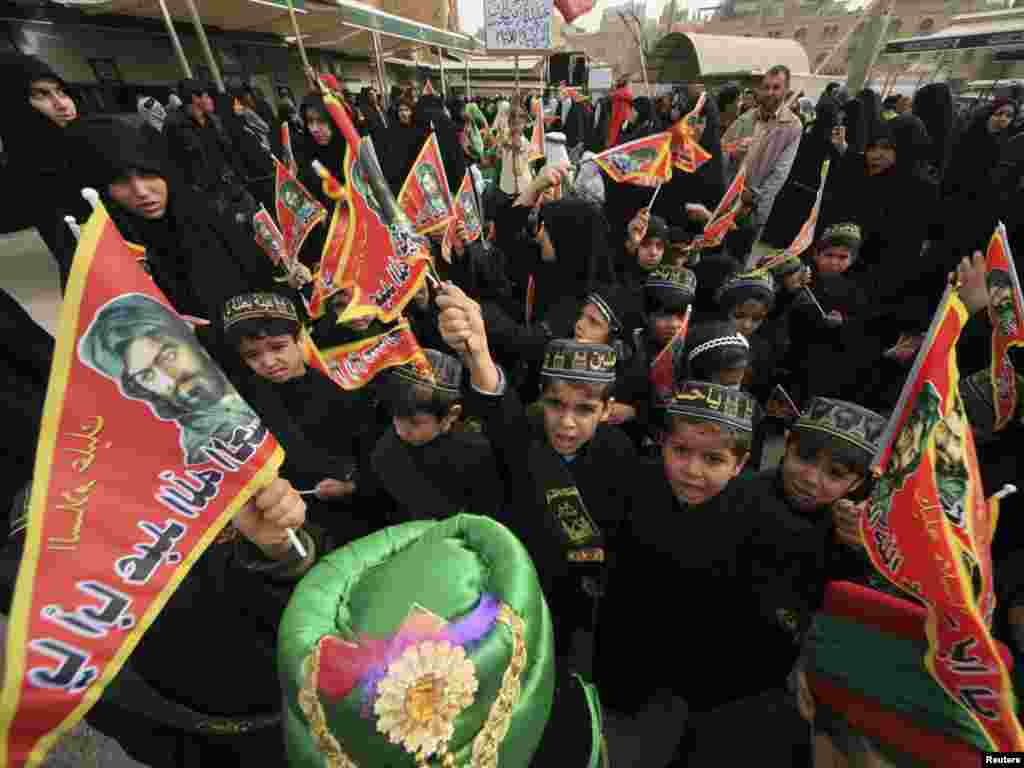 Children prepare for Ashura ceremony in Karbala, Iraq. They are wearing the traditional Muslim caps, taqiyah, inscribed for the occasion and waving banners that bear the likeness of Imam Hussein.