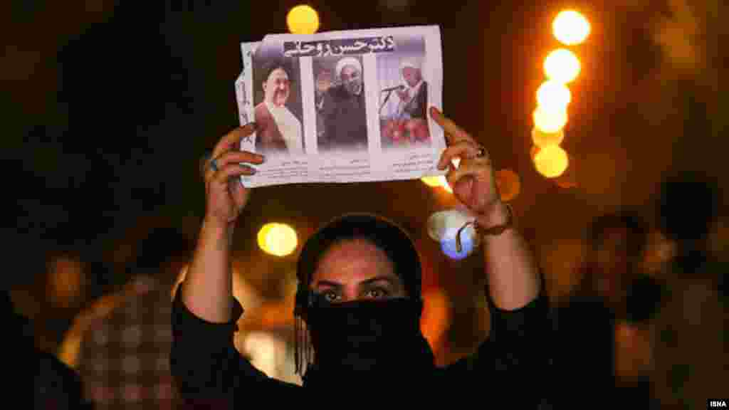 A woman displays images of pro-reform leaders who have allied themselves behind the candidacy of Hassan Rohani.