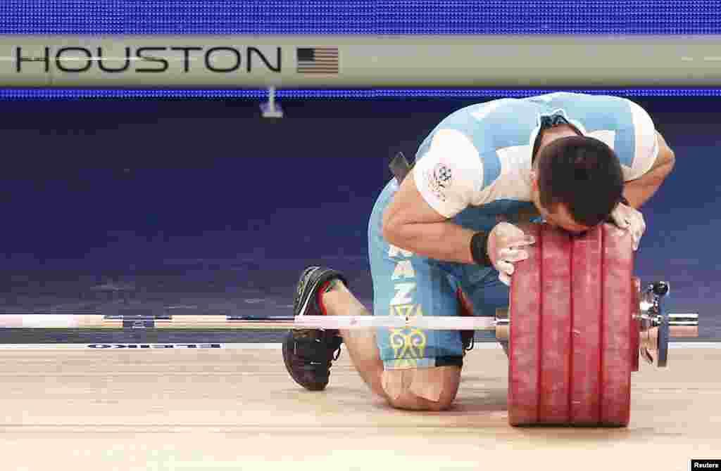 Алмас Утешов целует гири на штанге после завершения выступления. Он завоевывал второе место и в 2013 году на чемпионате мира в Польше, и в прошлом году на Азиатских играх.