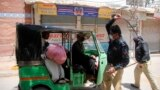 Police officers forcing a rickshaw driver to stop working during a nation-wide lockdown to curb the spread of the coronavirus in the southern city of Hyderabad in Sindh Province on April 3.