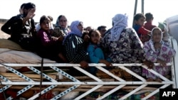 Syrians cross a checkpoint outside the northwestern Syrian city of Afrin, on the Syria-Turkey border, on August 23.