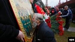 Відзначення дня народження Йосипа Сталіна на його могилі біля Кремлівської стіни на Червоній площі. Чоловік цілує ікону із зображенням радянського диктатора. Москва, 21 грудня 2015 року