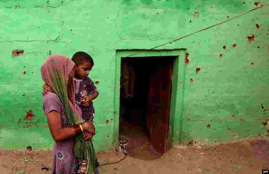 An Indian villager carries a child past a pock-marked house where four members of a family were reported to have been killed in cross-border exchanges, in Mashe de Kothe village, some 55 kilometers from Jammu.