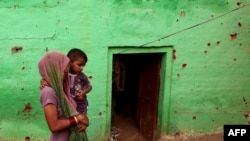 An Indian villager carries a child past a house where four members of a family were reported to have been killed in cross-border firing between Indian and Pakistani soldiers at Mashe de Kothe village in Arnia sector near the India-Pakistan border.