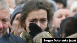 Një vajzë e re nga Ukraina qanë gjatë varrimit të shtatë shërbyesve civilë, të cilët u vranë në konfliktin në lindje të Ukrainës.