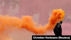 Парижде кәсіподақ шеруі кезінде қолына түтіндеткіш құты ұстаған демонстрант. Франция, 1 мамыр 2018 жыл.