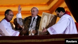 Newly elected Pope Francis (center) blesses the faithful on the balcony of St. Peter's Basilica after being elected by the conclave of cardinals on March 13.