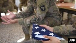 A U.S. soldier holds the national flag ahead of a handover ceremony at Leatherneck Camp in Lashkar Gah in Helmand, April 2017.