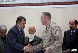 Міністр оборони Афганістану Бісмілла Могаммаді (л) і командувач Міжнародних сил сприяння безпеці генерал Джозеф Данфорд (п) після підписання угоди про передачу в'язниці, 25 березня 2013 року