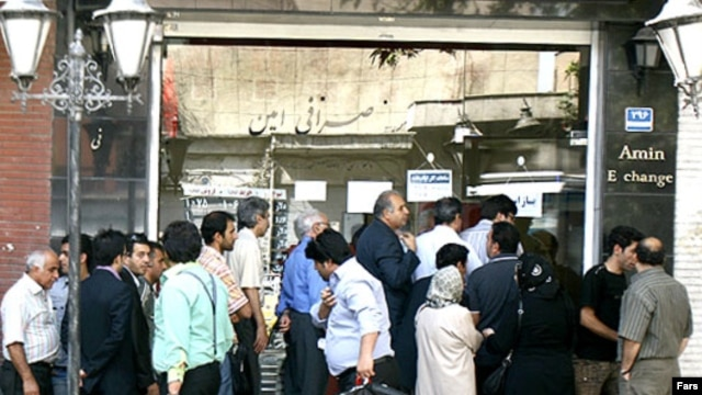 People stand in front of a currency exchange office in Tehran.