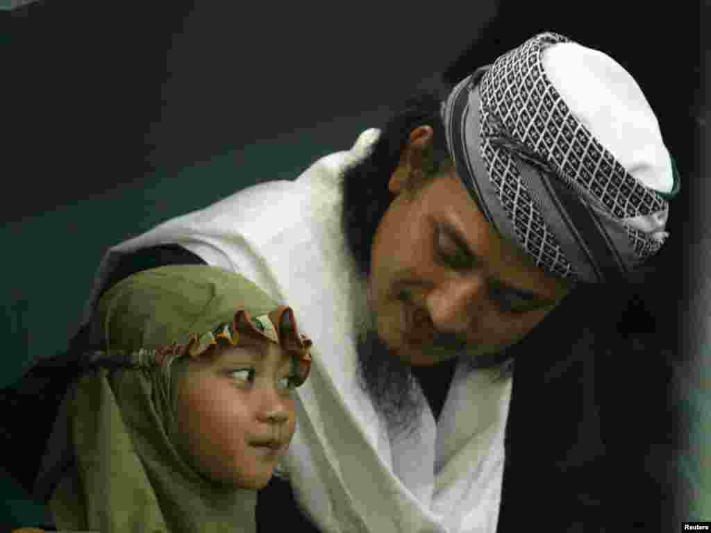Convicted Bali bomber Imam Samudera alias Abdul Aziz talks to his daughter during his last family visit in Batu prison, Nusa Kambangan Island, October 29, 2007. Three Indonesian militants on death row for their involvement in planning the Bali bombings five years ago said they were ready to die and would not seek a presidential pardon. REUTERS/Beawiharta