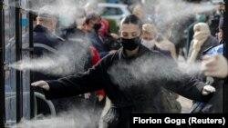 Qytetarët në Shqipëri kalojnë përmes një tuneli dezinfektues. Tiranë, 6 prill, 2020.