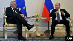 "Russian President Vladimir Putin (right) meets with European Commission President Jean-Claude Juncker in St. Petersburg on June 16. The policy document leaves an opening for improved relations between Brussels and Moscow, stating that ""the EU and Russia are interdependent."""
