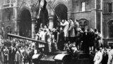 Budapestani cățărați pe un tanc sovietic în fața Parlamentului maghiar în timpul Revoluției maghiare, Budapesta 1956.