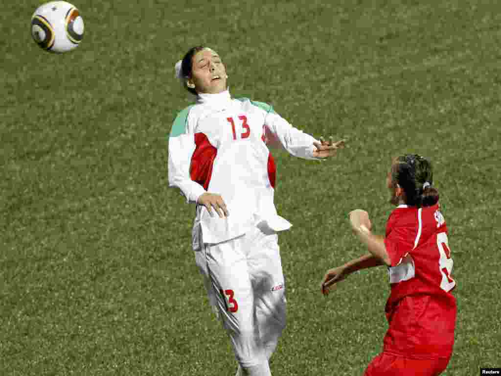 Iran's Fatemeh Shirafkannejad loses her head covering after she heads a ball during a match against Turkey at the Singapore Youth Olympic Games.
