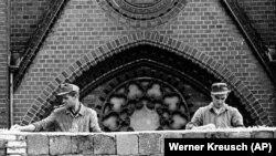 Soldați din Berlinul de est pun cioburi de sticlă pe zid pentru a preveni evadarea din Republica Democrată Germană. August 1961