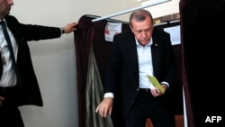 Turkish President Recep Tayyip Erdogan holds his vote for Turkey's general elections at a polling station in Istanbul on June 7.