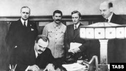 Veaceslav Molotov semnează Pactul de neagresiune cu Germania în prezența lui Stalin, la Moscova la 23 august 1939