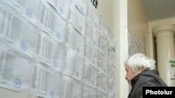 Ընտրություններ Հայաստանում. կինը քվեարկելուց առաջ ծանոթանում է ընտրատեղամասի պատին փակցված ընտրացուցակներին, արխիվ