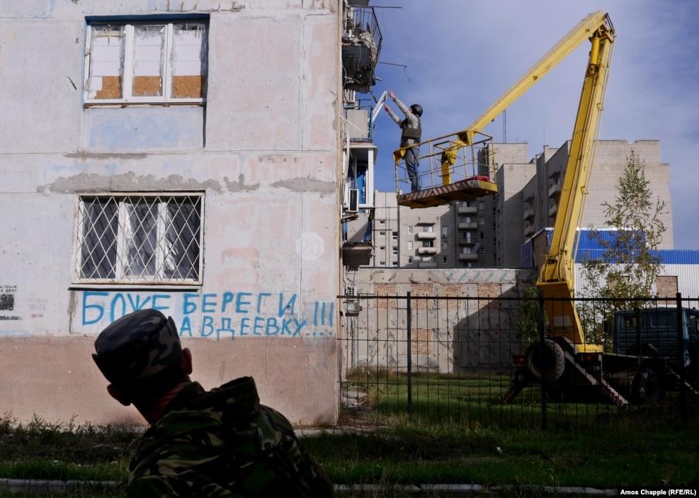 Поки ван Хелтен піднімається на своє робоче місце, український військовий проходить повз графіті: «Боже, борони Авдіївку»