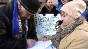 Чоловік підписує звернення до Київського міського голови Віталія Кличка під час акції «Закрити «Пташиний ринок»!» біля КМДА