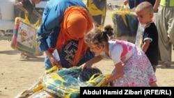 توزيع مساعدات على نازحين سوريين في مخيم كوروكوسك في اربيل