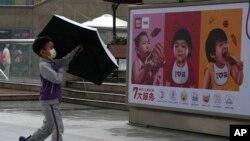 Дете се разхожда пред плакат в Китай. Снимката е илюстративна