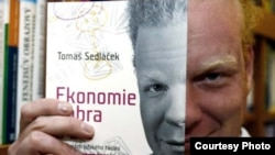 "Economist Tomas Sedlacek holds a Czech edition of his book ""The Economics of Good and Evil."""