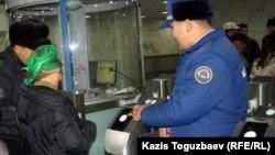 Пассажиры и сотрудник алматинского метро у турникета.
