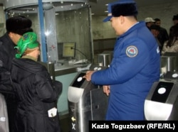 Жолаушылар метро турникеті арқылы өтіп жатыр. Алматы, 12 желтоқсан 2011 жыл.