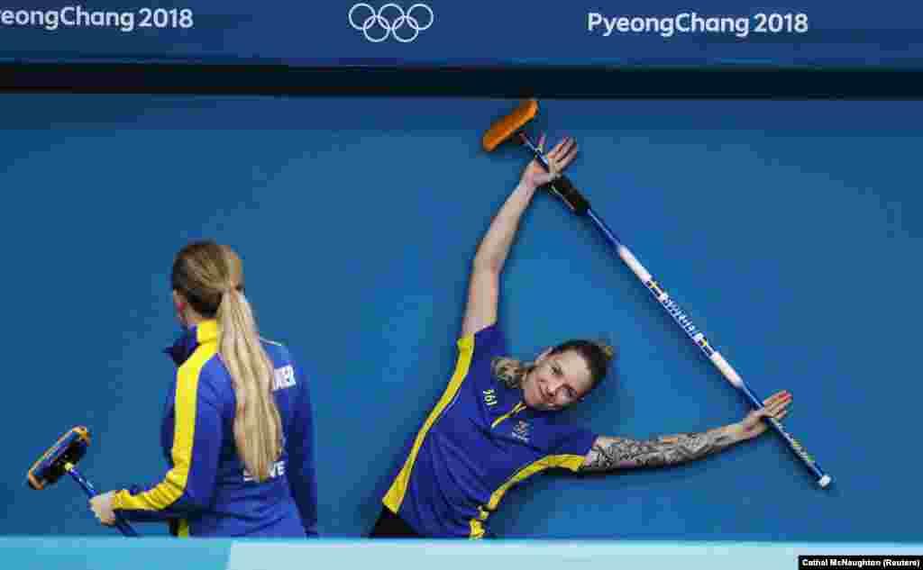 Керлинг: Агнес Кнохенхауэр и София Мабергс из Швеции растягиваются перед тренировочной сессией на ледовом катке в Канныне во время зимних Олимпийских игр в Пхенчхане
