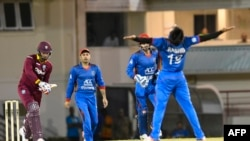 FILE: Kieran Powell (L) of West Indies caught by Afghanistan's Mohammad Nabi (C) bowled Rashid Khan Arman in a June one-day international competition.