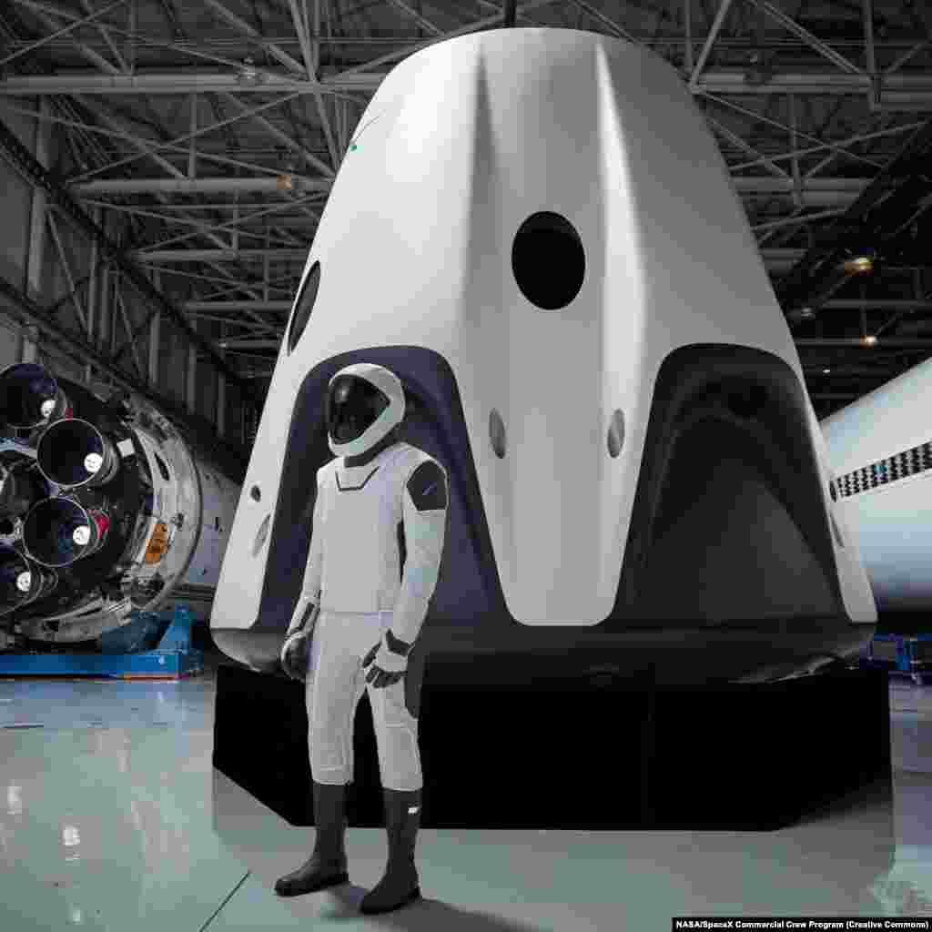 Демонстрація скафандру, призначеного для капсули Crew Dragon.  Цілісний костюм оснащений чобітками, які надійно закріплюються до сидіння Dragon, з вогнестійкою тефлоновою зовнішньою обшивкою і зручним сенсорним екраном під рукою