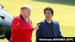 Japan's Prime Minister Shinzo Abe (R) listens to US President Donald Trump as they walk before playing a round of golf at Mobara Country Club in Chiba on May 26, 2019.