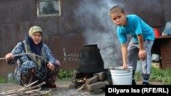 Жена и сын Зулкайнара Ергашева кипятят воду для чая на огне на улице, экономя газ. Семья переехала с юга на север Казахстана два месяца назад. Село Покровка, 21 июля 2016 года.