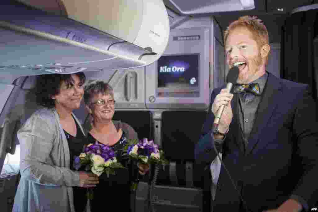 U.S. gay-rights campaigner and actor Jesse Tyler Ferguson (right) speaks in the skies above New Zealand during the same-sex marriage ceremony for Lynley Bendall (left) and Ally Wanikau on a flight from Queenstown to Auckland. New Zealand became the first Asia-Pacific country -- and only the 14th in the world -- to legalize gay marriage. (AFP)