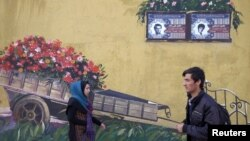 Прохожие в Тегеране у памятных досок с именами убитых в ирано-иракской войне 1980–1988 годов.
