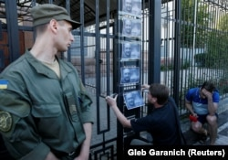 A man hangs photos of Babchenko on a fence outside the Russian Embassy in Kyiv on May 30.