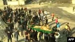 Syrian mourners carrying the coffin of a woman who was reportedly killed in the Hula region of central Homs province on December 12.