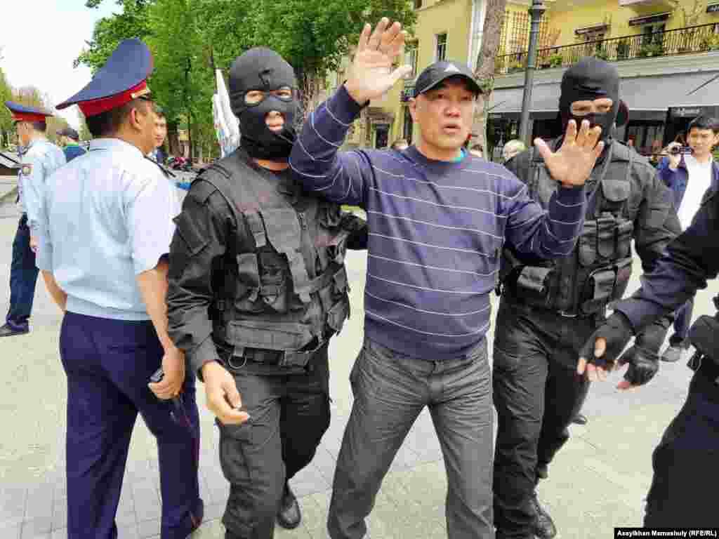 Қарсылық акциясына шыққан азаматты полиция әкетіп барады.