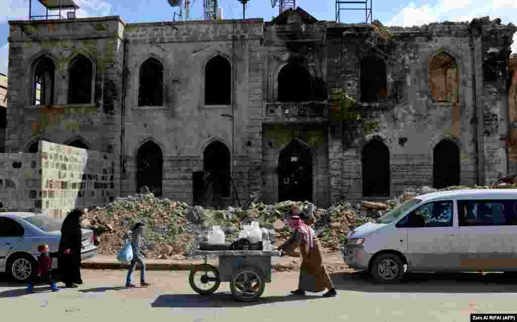 Вулічны разносчык штурхае пластыкавыя кантэйнеры па разбомбленай вуліцы ў сырыйскім горадзе Азазія, непадалёк ад турэцкай мяжы.