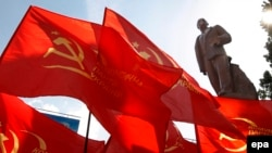 """Seeing red: Communist flags fly next to the same statue of Lenin in Kyiv in 2009, three years before the """"Euromaidan"""" unrest swept it off its feet."""