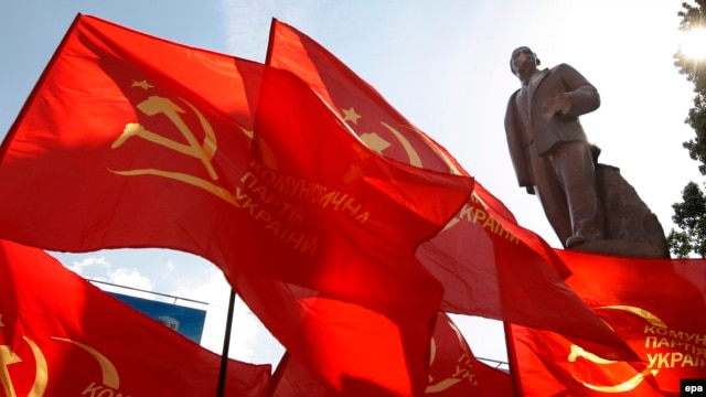 "Seeing red: Communist flags fly next to the same statue of Lenin in Kyiv in 2009, three years before the ""Euromaidan"" unrest swept it off its feet."