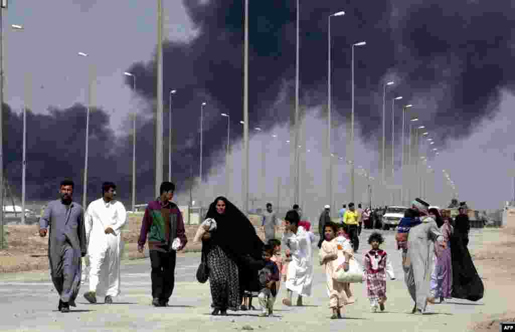 People flee the burning city of Basra, in southern Iraq, on March 28, 2003.