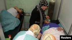 People injured in what the government said was a chemical-weapons attack breathe through oxygen masks as they are treated at a hospital in the city of Aleppo in March.