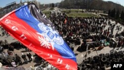 "The flag of the so-called ""Donetsk People's Republic"" flies above a barricade and a crowd gathered in front of the Donetsk regional administration building, which is being held by pro-Russian militants."