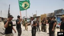 """Ополченцы """"Народной мобилизации"""" Ирака, поднимают флаг в городе Байджи, 8 июня 2015 года."""