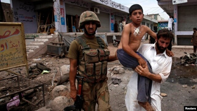A security official carries a boy injured in the  Peshawar attack on June 30.