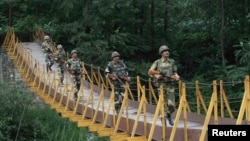 Indian Border Security Force (BSF) soldiers patrolling over a footbridge built over a stream near the Line of Control, a ceasefire line dividing Kashmir between India and Pakistan, in 2013.