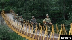 FILE: Indian Border Security Force (BSF) soldiers patrol over a footbridge built over a stream near the Line of Control (LoC), a ceasefire line dividing Kashmir between India and Pakistan.